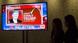 Two Japanese journalists watch the television screen image of Donald J Trump appears on a CNN program after the Republican party presidential nominee wins the vote from the state of Nebraska November 9, 2016 at the Hilton Hotel in New York City. (Photo by Robert Nickelsberg/Getty Images)