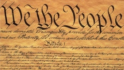 This is the Preamble to the US Constitution, It starts with the phrase We The People and shows only some of the writing from the upper left hand corner of the document of the Constitution, It is written on parchment paper that is now faded...