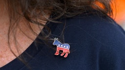 Donna Elms wears a Democrat donkey pin while lining up outside in advance of a campaign rally with former President Barack Obama, Pennsylvania Governor Tom Wolf, and Senator Bob Casey (D- PA) on September 21, 2018 in Philadelphia.