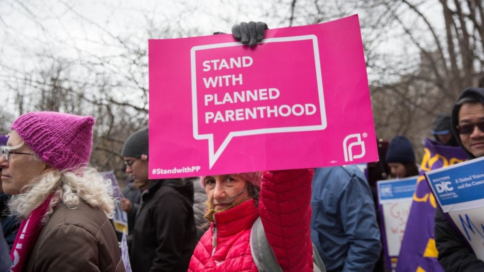"""A health care activist lifts signage promoting Planned Parenthood during a rally as part of the national """"March for Health"""" movement in front of Trump Tower on April 1, 2017 in New York City."""