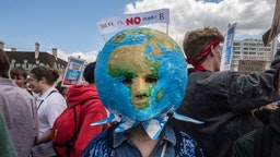 A striking school student with a planet mask on Westminster bridge on June 21, 2019 in London, England.