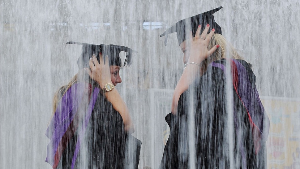 Students stand in a fountain ahead of their graduation ceremony at the Royal Festival Hall on July 15, 2014 in London, England.