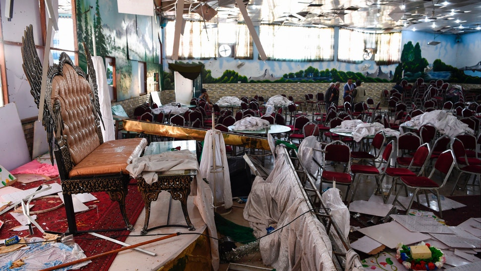 Afghan men investigate in a wedding hall after a deadly bomb blast in Kabul on August 18, 2019.