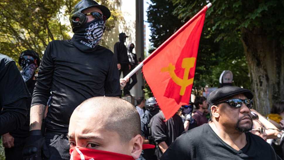 DOWNTOWN, PORTLAND, OREGON, UNITED STATES - 2018/08/04: Members of Antifa and other left-wing protesters watch far right protesters on the other side of the street during the Patriot Prayer Rally. The Proud Boys organized the Patriot Prayer Rally in Portland. The Proud Boys, a far right group supportive of President Donald Trump, used inflammatory language ahead of their rally, with some members promising violence. Counter-protesters led by Antifa confronted the participants of the Patriot Prayer Rally and clashed with police, leading to arrests and injuries.
