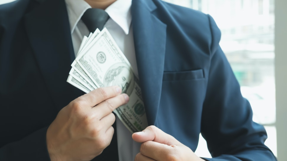 Midsection Of Businessman Putting Money Into Pocket