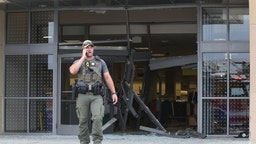 A state police officer stands outside of a Woodfield Mall entrance on Friday, Sept. 20, 2019, in Schaumberg, Ill. A vehicle drove into the mall on Friday through one of the Sears' entrances.