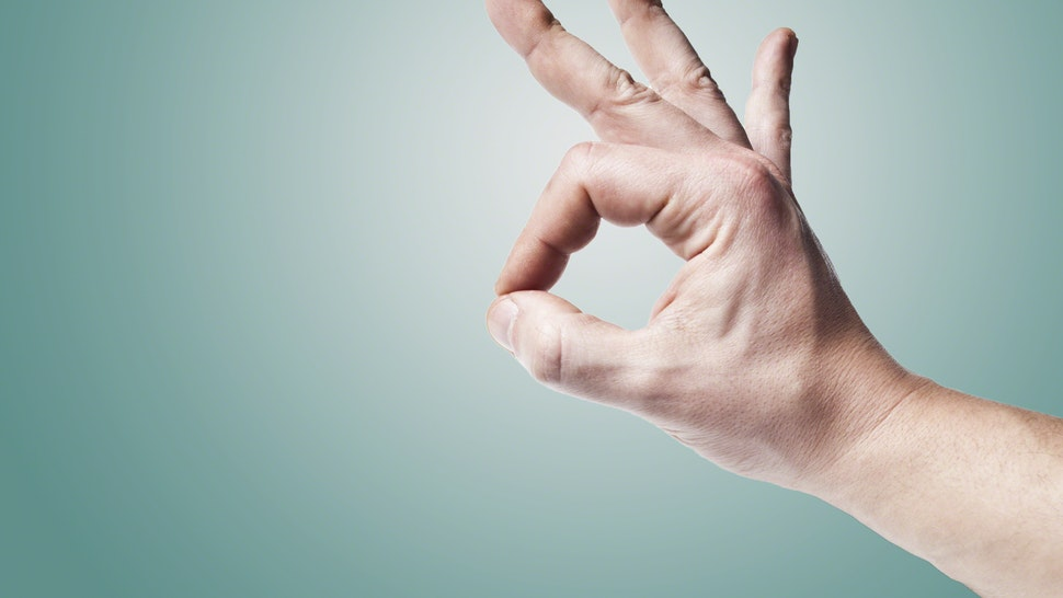 Male hand forming OK sign