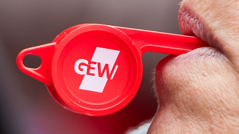 20 February 2019, Hamburg: A participant in a warning strike by collective bargaining employees at schools and universities in Hamburg stands in front of the tax authorities and blows a whistle with the logo of the GEW trade union. In the wage dispute in the public sector, the unions demand six percent more money, but at least 200 euros more per month.
