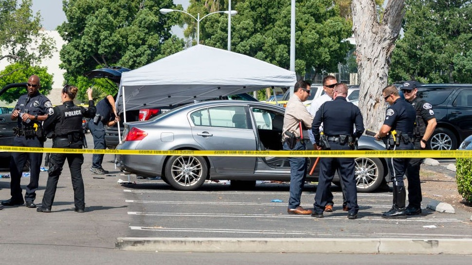 Police investigate a car where a retired Cal State Fullerton administrator was stabbed to death Monday, August 19, 2019 in Fullerton, CA.