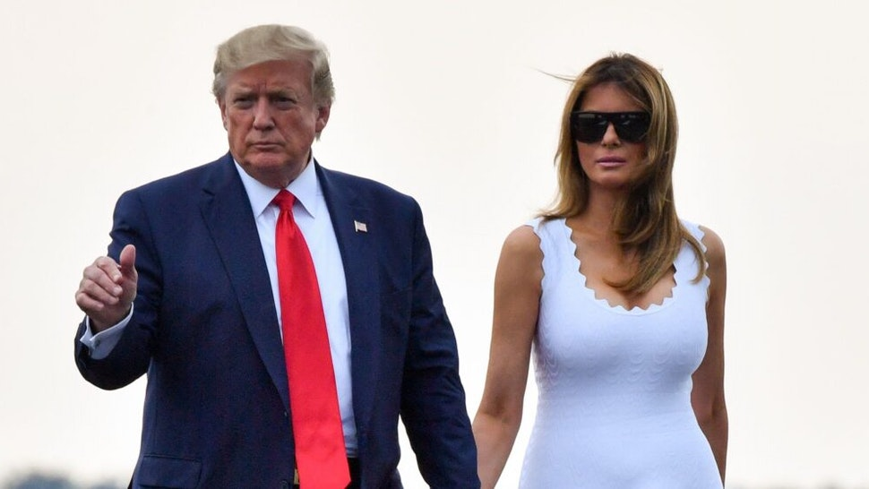 US President Donald Trump (L) and US First Lady Melania Trump walk toward Air Force One in Bordeaux, south-west France on August 26, 2019, after attending the annual G7 Summit in Biarritz. (Photo by Nicholas Kamm / AFP)