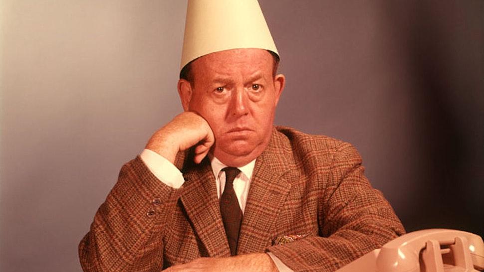 1960s sad, depressed man wearing a dunce cap.