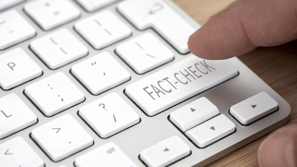 "Finger about to press a key labeled ""fact check"" on a computer keyboard."