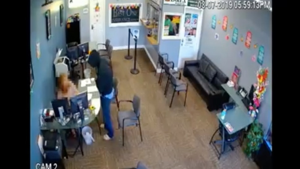 The moment a knife-wielding man attacks an employee of an insurance company.