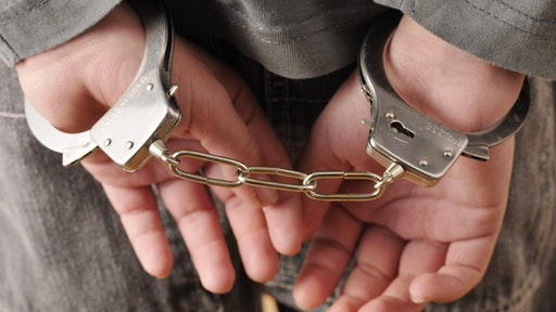 Close-up of Handcuffs on Boy's Wrists - stock photo