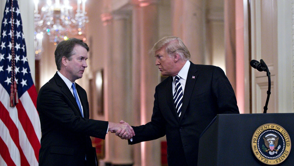 U.S. President Donald Trump, right, shakes hands with Brett Kavanaugh, associate justice of the U.S. Supreme Court, during a ceremonial swearing-in event in the East Room of the White House in Washington, D.C., U.S., on Monday, Oct. 8, 2018.