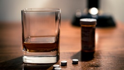 Opiate pills and alcohol epidemic -- close up of pills and glass of booze.