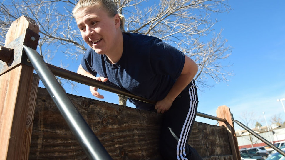 Longmont Police Explorer graduate Katie Schultz scales a six foot wall on the department's obstacle course Wednesday during an annual fitness test. (Photo by Lewis Geyer/Digital First Media/Boulder Daily Camera via Getty Images)