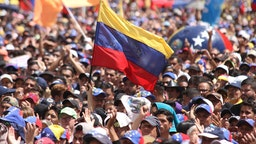 12 February 2019, Venezuela, Caracas: Numerous people take part in a rally of government opponents in the Venezuelan capital. Thousands of people took to the streets again in the power struggle between the Venezuelan head of state Maduro and the self-proclaimed interim president Guaido. On the occasion of Youth Day, they called on the armed forces to open the borders and enable the delivery of relief supplies to the suffering population.