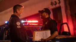 An ICE agent with U.S. Homeland Security Investigations (HSI), (L) and a Guatemalan policeman speak at the scene of a raid where a suspected human trafficker was taken into custody on May 29, 2019 in Guatemala City.