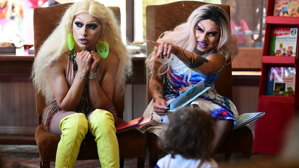 Drag queen Scalene Onixxx (R) gestures seated beside Athena Kills while reading during Drag Queen Story Hour at Cellar Door Books in Riverside, California on June 22, 2019. - Athena and Scalene, their long blonde hair flowing down to their sequined leotar