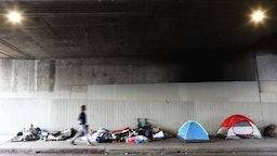 LOS ANGELES, CALIFORNIA - JUNE 05: A man walks past a homeless encampment beneath an overpass on June 5, 2019 in Los Angeles, California. The homeless population count in Los Angeles County leaped 12 percent in the past year to almost 59,000, according to officials.