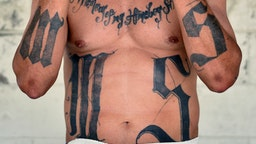 """Former MS-13 gang leader Valmis Mejia a.k.a. 'el Bambi', is pictured at Santa Ana prison, 60 km northwest of San Salvador, on May 21, 2019. - Former members of Salvadoran gangs -mostly of the Mara Salvatrucha (MS-13) and Barrio 18- claim to be willing to endure a painful process with laser technology, that can take years, to erase tattoos they now say were a """"youth mistake"""". ("""