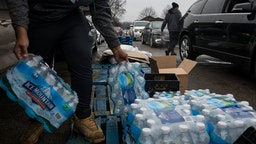 FLINT, MICHIGAN - DECEMBER 20: Workers load bottled water into vehicles waiting in line at a water distribution site at Greater Holy Temple in Flint, Mich., on Thursday, December 20, 2018.