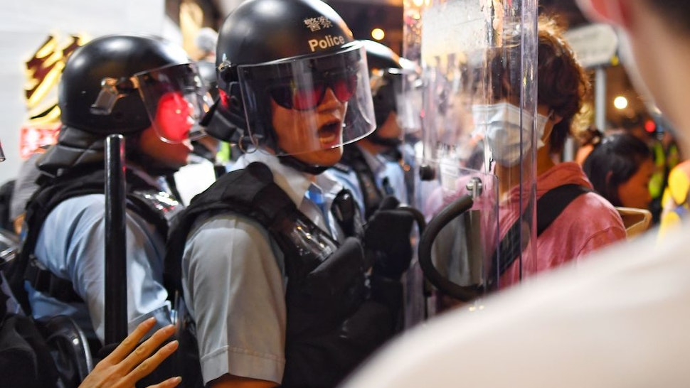 A Police man (L) shouts at a Pro-Democracy Protestor (R) to move out of his way during a gathering in the Sham Shui Po Area of Hong Kong on August 14, 2019. - More than 10 weeks of sometimes-violent demonstrations have wracked the semi-autonomous city, with millions taking to the streets to demand democratic reforms and police accountability.