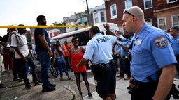 Police officers direct citizens to move back near the scene of a shooting on August 14, 2019 in Philadelphia, Pennsylvania. At least six police officers were reportedly wounded in an hours-long standoff with a gunman that prompted a massive law enforcemen