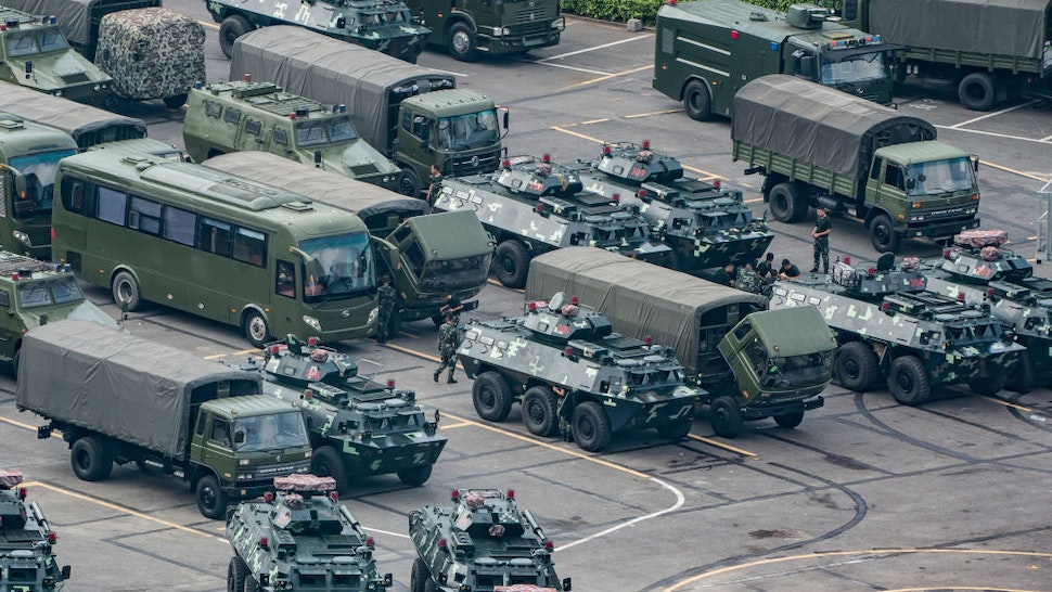 """SHENZHEN, CHINA - AUGUST 16: Chinese military personnel maintain trucks and armoured personnel vehicles parked outside the Shenzhen Bay stadium on August 16, 2019 in Shenzhen, China. Pro-democracy protesters have continued rallies on the streets of Hong Kong against a controversial extradition bill since 9 June as the city plunged into crisis after waves of demonstrations and several violent clashes. Hong Kong's Chief Executive Carrie Lam apologized for introducing the bill and declared it """"dead"""", however protesters have continued to draw large crowds with demands for Lam's resignation and completely withdraw the bill."""
