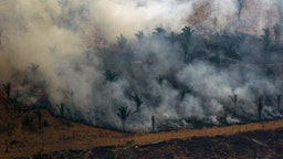 TOPSHOT - Aerial view showing smoke billowing from a patch of forest being cleared with fire in the surroundings of Boca do Acre, a city in Amazonas State, in the Amazon basin in northwestern Brazil, on August 24, 2019. - Brazil on August 25 deployed two Hercules C-130 aircraft to douse fires devouring parts of the Amazon rainforest. The latest official figures show 79,513 forest fires have been recorded in the country this year, the highest number of any year since 2013. More than half of those are in the massive Amazon basin. Experts say increased land clearing during the months-long dry season to make way for crops or grazing has aggravated the problem this year.