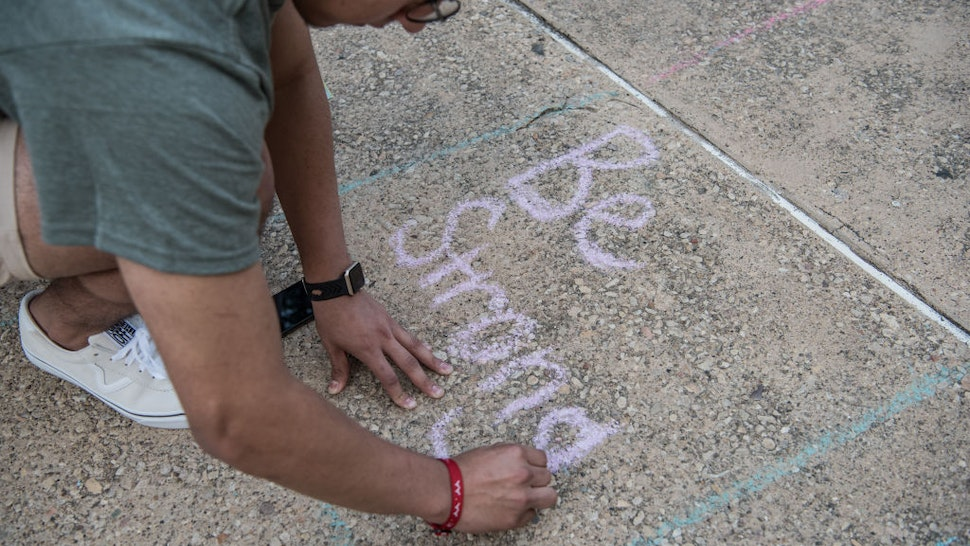 Juan Perez, 17, writes with chalk during a vigil at the University of Texas of the Permian Basin (UTPB) for the victims of a mass shooting, September 1, 2019 in Odessa, Texas.