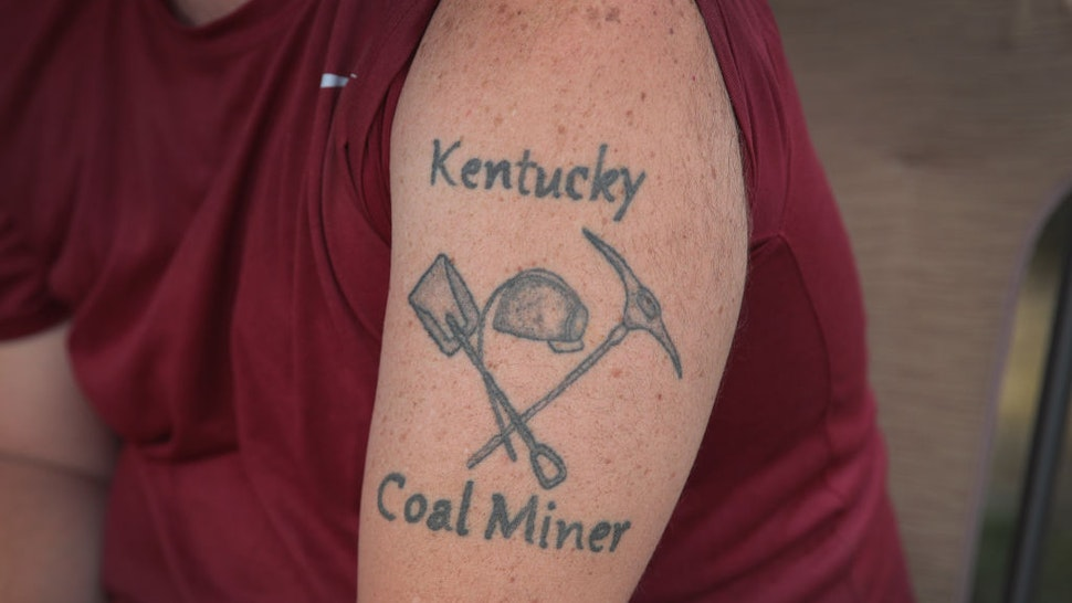 CUMBERLAND, KENTUCKY - AUGUST 08: Unemployed Blackjewel coal miner Chris Lewis shows his tattoo as he participates in a blockade along the railroad tracks that lead to one of Blackjewel's mines on August 08, 2019 near Cumberland, Kentucky. The Blackjewel miners of Harlan County unexpectedly found themselves unemployed when Blackjewel declared bankruptcy and shut down their mines. Just as unexpected was the discovery that the miner's final paychecks had bounced. When a few of the miners learned the company was shipping out a final load of coal by rail they decided to blockade the tracks to prevent the shipment from leaving the mine until they were paid their wages. The blockade, which is in its 11th day, has received a local and national outpouring of support.