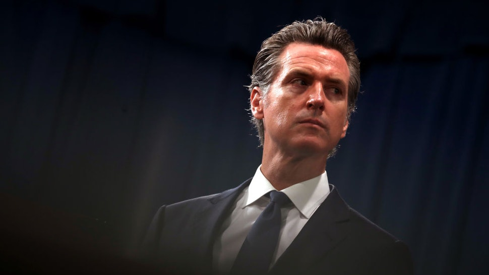 """SACRAMENTO, CALIFORNIA - AUGUST 16: California Gov. Gavin Newsom looks on during a news conference with California attorney General Xavier Becerra at the California State Capitol on August 16, 2019 in Sacramento, California. California attorney genera Xavier Becerra and California Gov. Gavin Newsom announced that the State of California is suing the Trump administration challenging the legality of a new """"public charge"""" rule that would make it difficult for immigrants to obtain green cards who receive public assistance like food stamps and Medicaid."""
