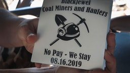 CUMBERLAND, KENTUCKY - AUGUST 24: Chris Rowe, an unemployed Blackjewel coal miner, shows off stickers that were made for the miners while he mans a blockade of the railroad tracks that lead to the mine where he once worked on August 24, 2019 in Cumberland, Kentucky. More than 300 miners in Harlan County unexpectedly found themselves unemployed when Blackjewel declared bankruptcy and shut down their mining operations.