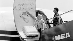 A Lebanese woman cleans the slogans which have been writting by the hijackers on the door of the TWA plane, on July 6, 1985 at Beirut airport.