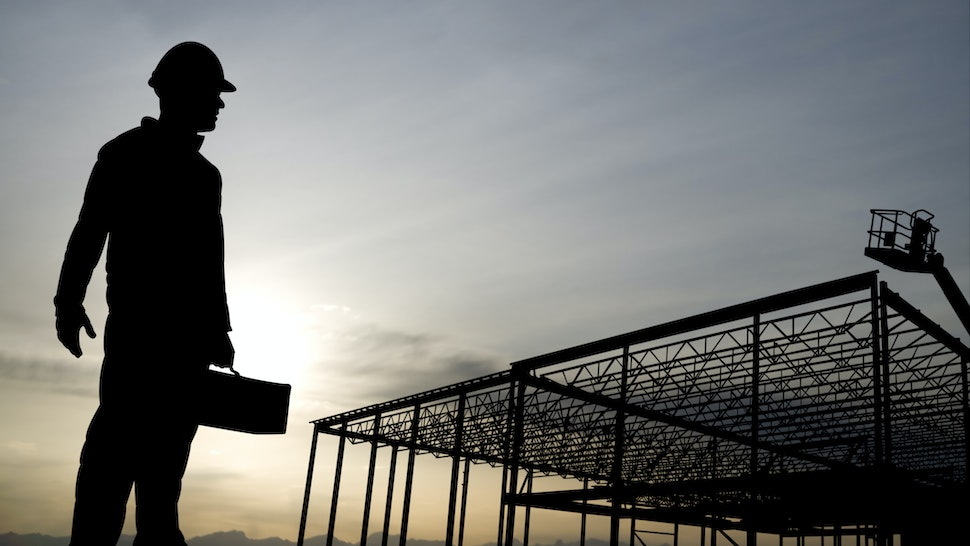 A construction worker heads off to work at dawn.
