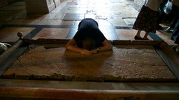Stone of the Anointing (or Unction) in Church of the Holy Sepulchre, Pilgrim praying, Old City of Jerusalem (Unesco World Heritage List, 1981), Israel.