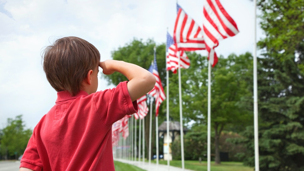 A young boy salutes the flags of a Memorial Day display along a small town street
