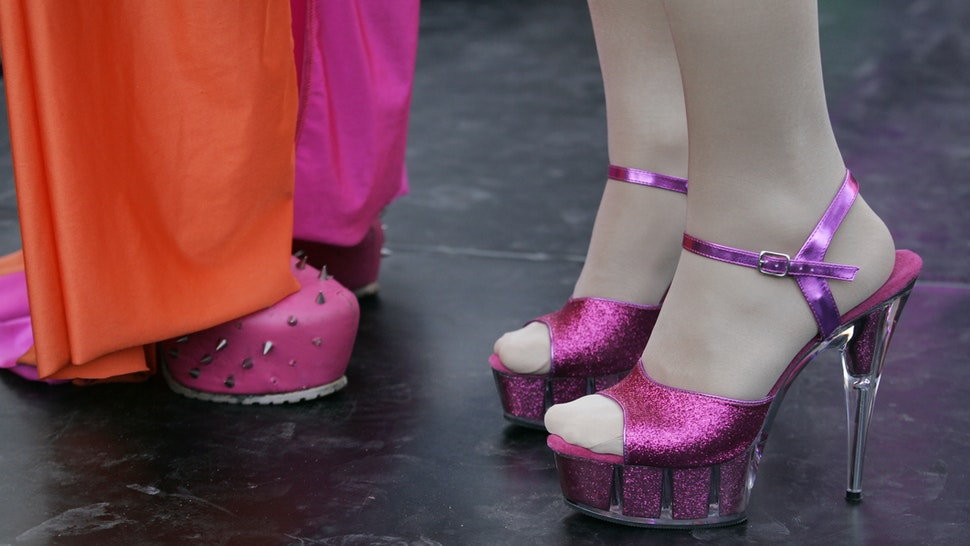 Drag queens performs on the street with pink high heel shoe during Gay Pride Parade in Amsterdam,Netherlands.