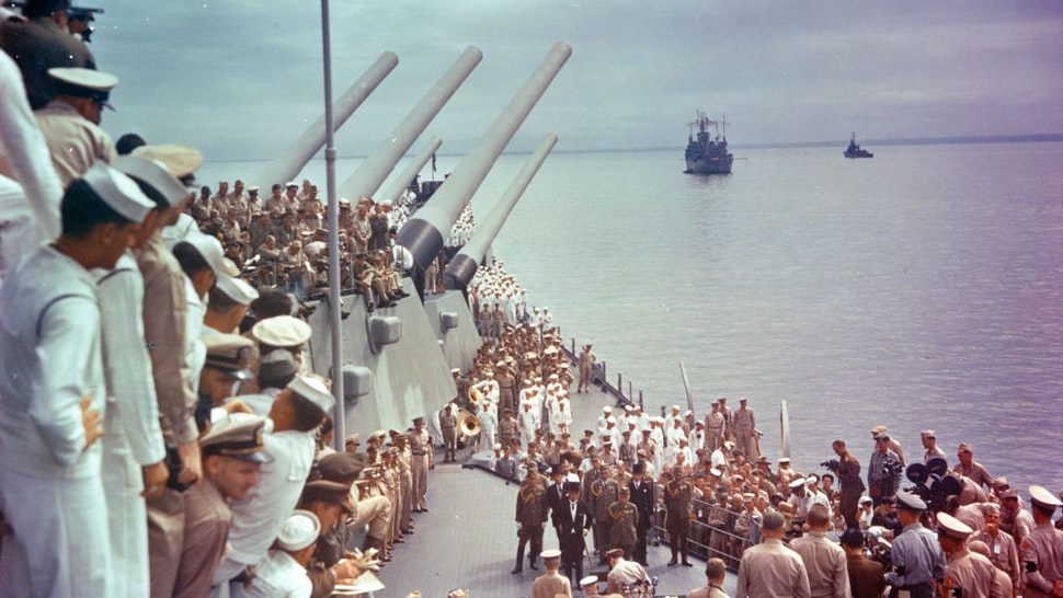 General view of US sailors as they watch the signing of the Japanese Instrument of Surrender (which ended World War II) on the deck of the USS Missouri, anchored in Tokyo Bay, Japan, September 2, 1945. Dutch Lieutenant-Admiral Conrad Helfrich (1886 - 1962) (seated at table, center bottom) is signing as, among those also pictured, US General Douglas MacArthur (1880 - 1964) (standing to Helfrich's right) and the members of the Japanese delegation watch. They are, front row from left Japanese Minister of Foreign Affairs Mamoru Shigemitsu (1887 - 1957) (with cane) and Chief of the General Staff General Yoshijiro Umezu (1882 - 1949); second row, Major General Yatsuji Nagai (1901 - 1970), Foreign Minister Katsuo Okazaki (1897 - 1965), Rear Admiral Tadatoshi Tomioka (1897 - 1970), Foreign Minister Toshikazu Kase (1903 - 2004), and Lieutenant General Suichi Miyakazi (1895 - 1969); third row, Rear Admiral Ichiro Yokoyama (1900 - 1993), Foreign Minister Saburo Ohta, Captain Katsuo Shiba (1901 - 1970), and Colonel Kaziyi Sugita (1904 - 1993).
