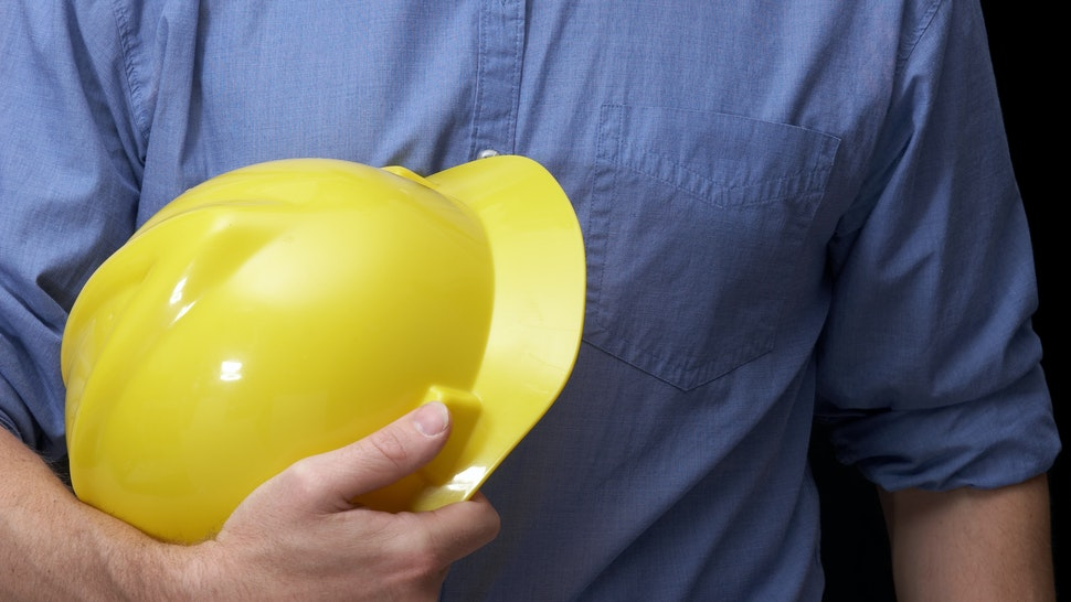 Torso of a man with yellow hardhat and blue work shirt