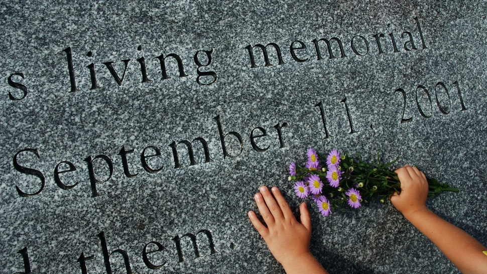 Child places flowers on 9/11 Memorial