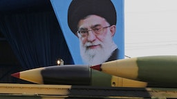Rouhani's photo set behind image of weapons in Iran