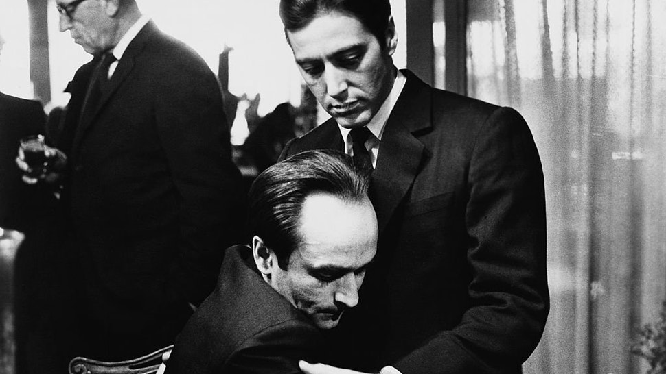 """Frederico """"Fredo"""" Corleone (John Cazale) holds his brother Michael Corleone (Al Pacino) at a family funeral in Francis Ford Coppola's The Godfather: Part II."""