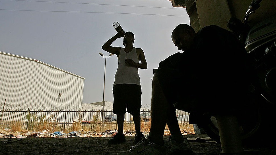 srael and Erasmus, a pair of homeless drug addicts, share a boittle of malt liquor at their encampment in downtown Los Angeles.