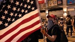 Demonstrator waves an American flag during the protest. KOWLOON, HONG KONG, HONG KONG SAR, CHINA
