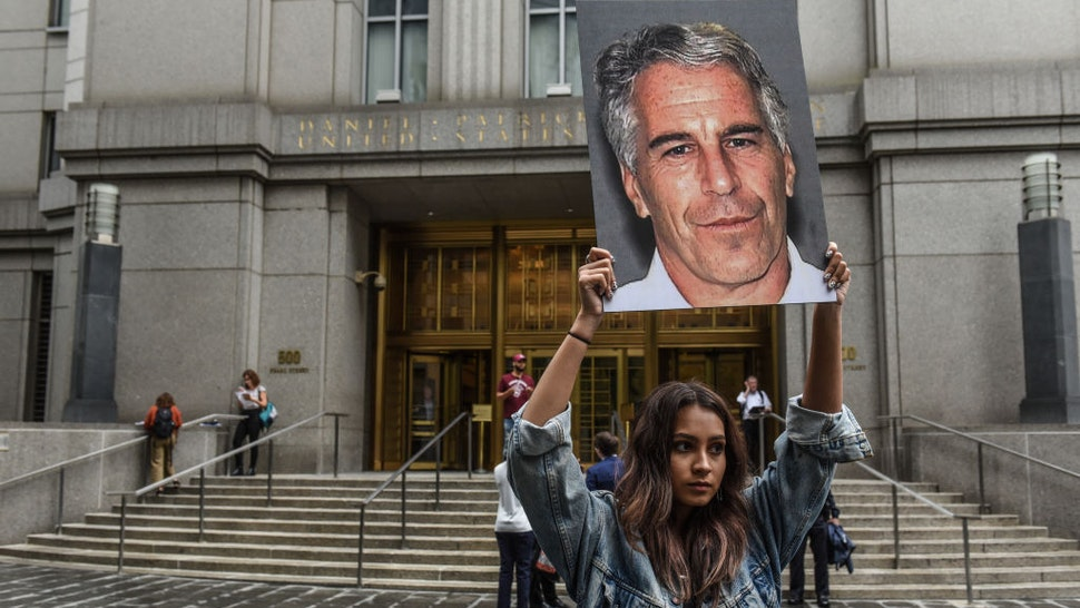 "A protest group called ""Hot Mess"" hold up signs of Jeffrey Epstein in front of the federal courthouse on July 8, 2019 in New York City."