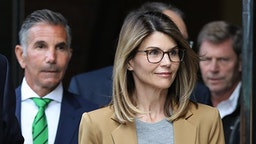 Actress Lori Loughlin and her husband Mossimo Giannulli, wearing green tie at left, leave the John Joseph Moakley United States Courthouse in Boston on April 3, 2019.