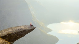Woman sitting on Trolltunga at Odda, Hordaland county, Norway.